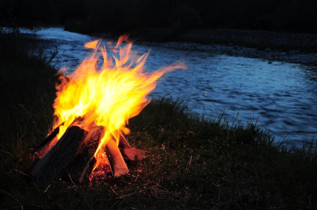 image showing a fire at night beside a river